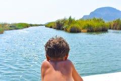 Jongen op de boot, die in de rivier vooruitgaan royalty-vrije stock afbeeldingen