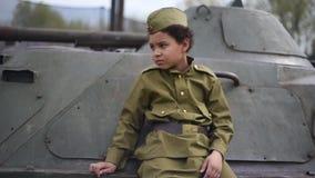 Jongen op de oorlog Kindschooljongen op een tank De jongen in de vorm van een militair tijdens de Tweede wereldoorlog van 1941-19 stock video