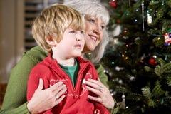 Jongen op de overlapping van de grootmoeder door Kerstboom stock foto