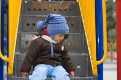 Jongen op de speelplaats Stock Foto