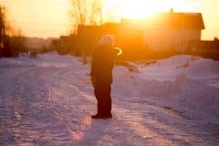 Jongen op de weg in de winter bij zonsondergang stock afbeelding