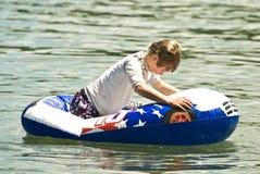 Jongen op een Vlotter in het Water Stock Fotografie