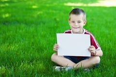 Jongen op groene weide met een wit blad van document Royalty-vrije Stock Afbeeldingen