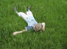 Jongen op het groene gras stock foto's
