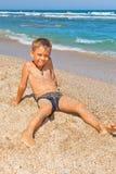 Jongen op het strand met overzees op achtergrond Royalty-vrije Stock Afbeeldingen