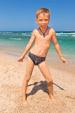 Jongen op het strand met overzees op achtergrond Stock Afbeeldingen