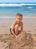 Jongen op het strand met zand Royalty-vrije Stock Foto's