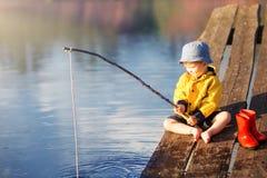 Jongen op houten dok met een visnet stock afbeeldingen