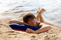 Jongen op luchtbed bij zonnig strand Royalty-vrije Stock Foto's