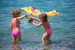 Jongen op opblaasbare matras in overzees en meisjes dichtbij Royalty-vrije Stock Afbeeldingen