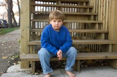 Jongen op portiekstappen Stock Afbeeldingen