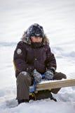 Jongen op schommeling in de winter Stock Foto