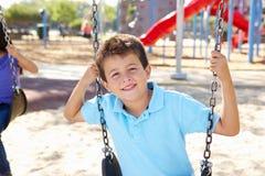 Jongen op Schommeling in Park Stock Fotografie
