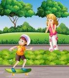 Jongen op skateboard en moeder in het park Stock Foto