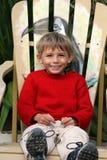 Jongen op stoel Stock Foto's