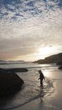 Jongen op strand bij zonsondergang Stock Foto's