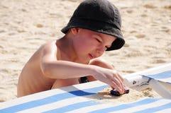 Jongen op strand het spelen in het zand Stock Foto's