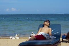 Jongen op tropisch strand Stock Foto's