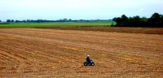 Jongen op vierling door het landbouwbedrijf Stock Foto