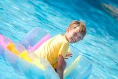 Jongen op vlotter zwembad stock foto