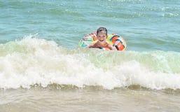 Jongen in opblaasbare ring die op het overzees al nat drijven en gelukkig, Stock Fotografie