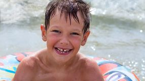 Jongen in opblaasbare ring die op het overzees al nat drijven en gelukkig Stock Foto's
