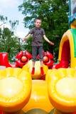 Jongen in opblaasbare speelplaats Stock Fotografie