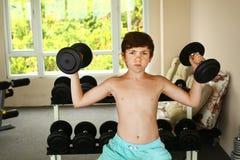 jongen opleiding met domoren in gymnastiek Stock Afbeelding