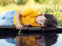 Jongen in parkspel met boot in rivier royalty-vrije stock afbeeldingen