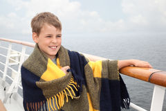 Jongen in plaid op dek van schip Royalty-vrije Stock Afbeeldingen