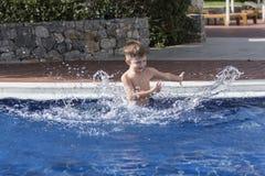 Jongen plaiyng in zwembad stock afbeelding