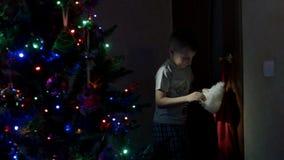 Jongen in pyjama's die tot de Kerstmissok heimelijk nemen stock videobeelden