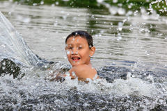 Jongen in rivier Stock Foto