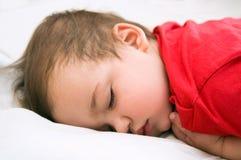 Jongen in rode kledingsslaap op bed Royalty-vrije Stock Afbeeldingen