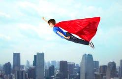 Jongen in rode superherokaap en masker die op lucht vliegen Royalty-vrije Stock Foto's