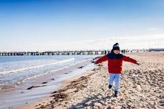 Jongen in rood jasje die op strand lopen stock afbeeldingen
