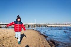 Jongen in rood jasje die op strand lopen stock fotografie