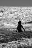 Jongen in ruwe branding bij het strand in zwart-wit Royalty-vrije Stock Foto