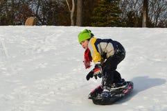 Jongen Snowboarding op een Slee in de Winter stock afbeeldingen