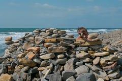 Jongen spelen, die achter een vesting van stenen op het overzeese kuststrand verbergen royalty-vrije stock afbeeldingen