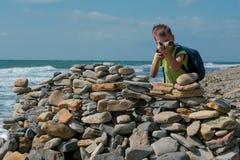 Jongen spelen, die achter een vesting van stenen op het overzeese kuststrand verbergen stock afbeelding