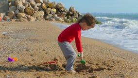 Jongen in spelen het buiten het seizoen op het strand stock footage