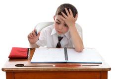 Jongen thinkinhg bij schoolbank royalty-vrije stock afbeelding