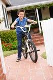 Jongen in tuin met fiets Stock Fotografie