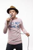 Jongen van de zanger de donkerbruine tiener in roze Jersey in gouden hoed met een microfoon Royalty-vrije Stock Foto's