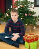 Jongen voor Kerstmisboom met zijn nieuwe tabletpc Stock Foto's