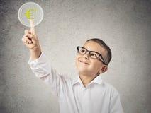 Jongen wat betreft geel euro muntteken royalty-vrije stock foto's