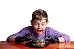 Jongen in zwarte handschoenen die emotioneel een hamburger eten royalty-vrije stock afbeeldingen