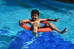Jongen in zwembad met veiligheidswachten Stock Afbeeldingen