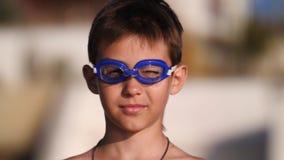 Jongen in zwemmende beschermende brillen op het strand die de camera en het glimlachen bekijken royalty-vrije stock afbeeldingen